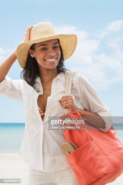 black woman carrying tote bag on beach - woman carrying tote bag stock photos and pictures
