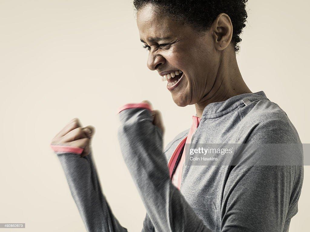Black woman celebrating in exercise top : ストックフォト