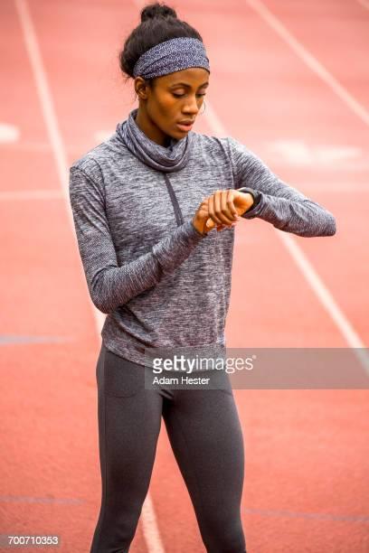 black woman checking smart watch on track - オリンピック選手 ストックフォトと画像