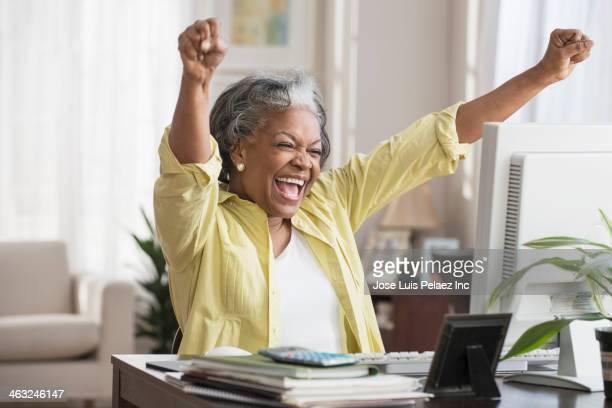 Black woman cheering at computer