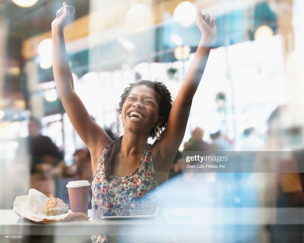 Black woman cheering in cafe : Stock Photo