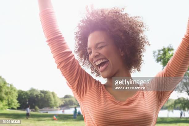 Black woman cheering outdoors