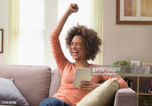 Black woman cheering with digital tablet on sofa
