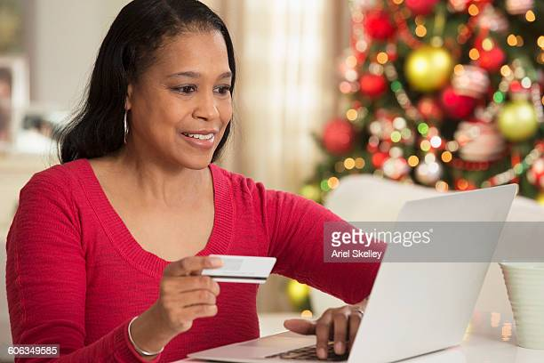black woman christmas shopping on laptop - black friday stock photos and pictures