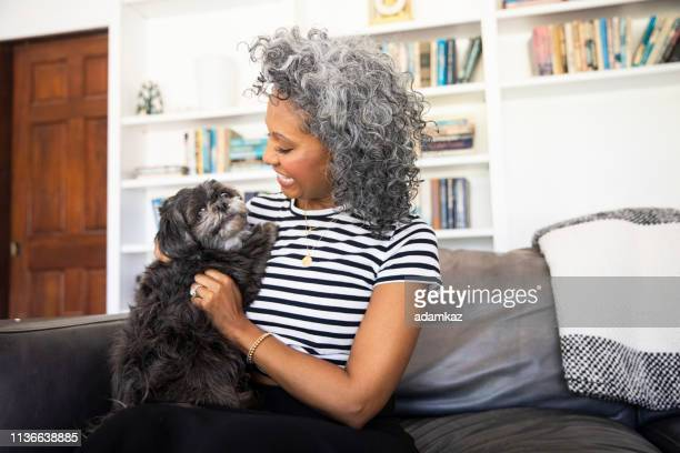 Black Woman Cuddles with her dog at home