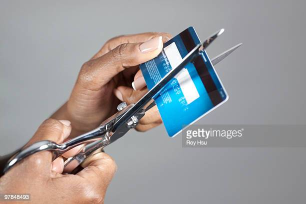 Black woman cutting credit card with scissors