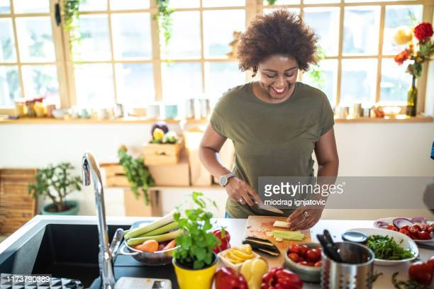 black woman cutting vegetables in kitchen - chopping food stock pictures, royalty-free photos & images