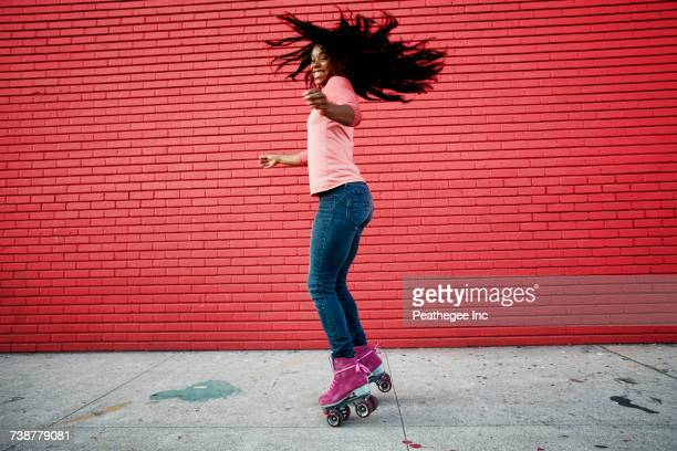 Black woman dancing on roller skates on sidewalk