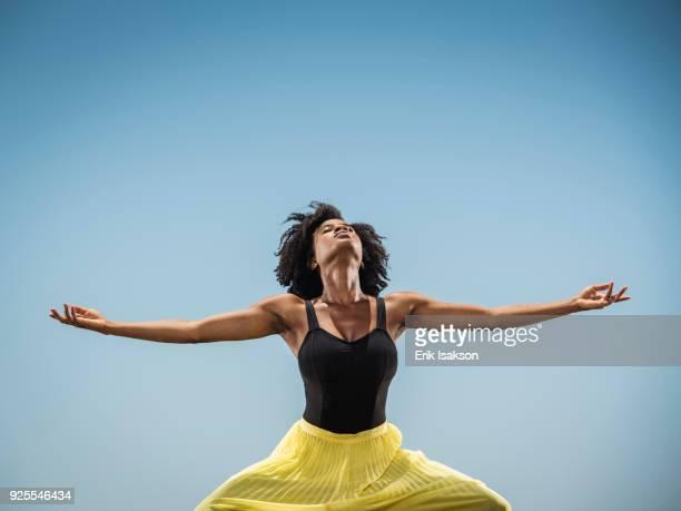 black woman dancing with arms outstretched - performer stock pictures, royalty-free photos & images