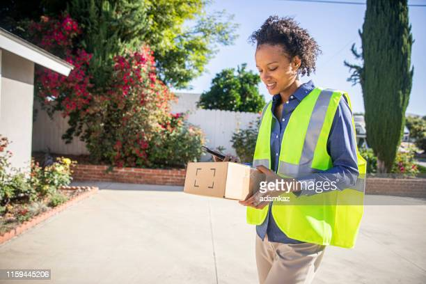 black woman delivering package - postal worker stock pictures, royalty-free photos & images