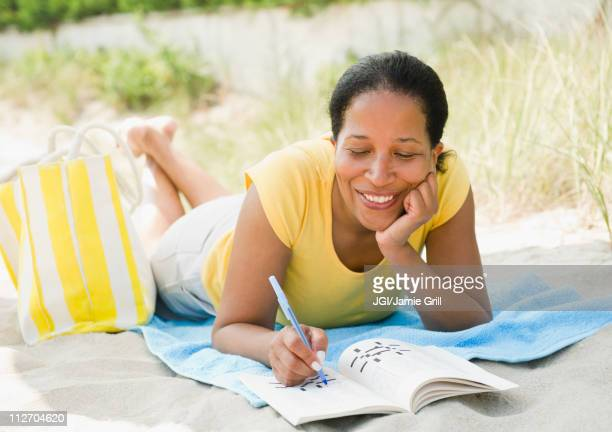 Black woman doing crossword puzzle on beach