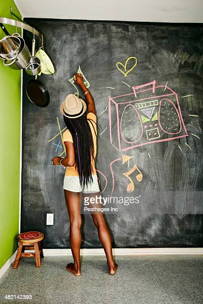 Black woman drawing on blackboard wall