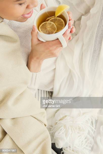 Black woman drinking cup of tea with lemon
