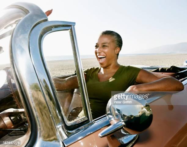 Black woman driving convertible