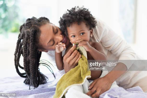 Black woman drying baby daughter with towels