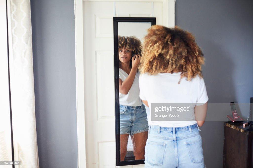 Black woman examining hair in mirror : Stock Photo