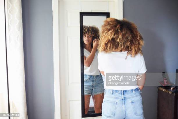 black woman examining hair in mirror - looking stock pictures, royalty-free photos & images