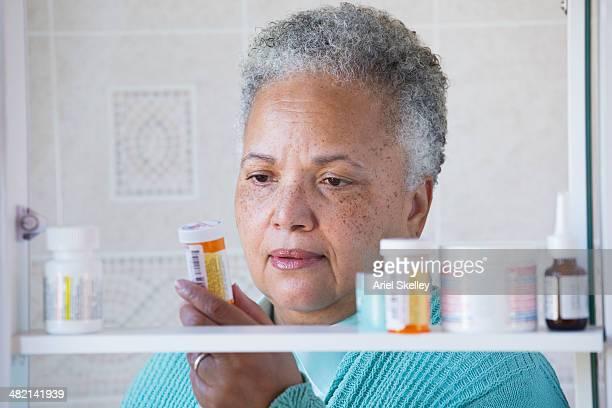 black woman examining prescription bottle in medicine cabinet - armoire de toilette photos et images de collection