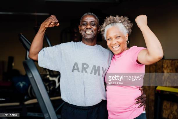 black woman flexing muscles in garage - flexing muscles stock pictures, royalty-free photos & images