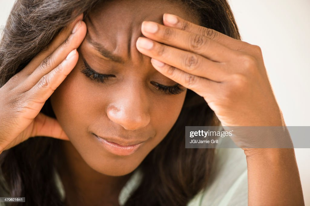 Black woman frowning with head in hands : Stock Photo