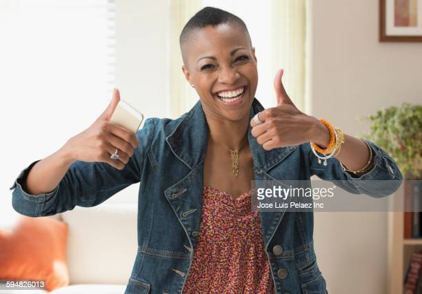 Black woman giving thumbs up in living room