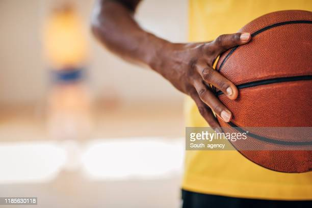 black woman holding a basketball ball - women's basketball stock pictures, royalty-free photos & images