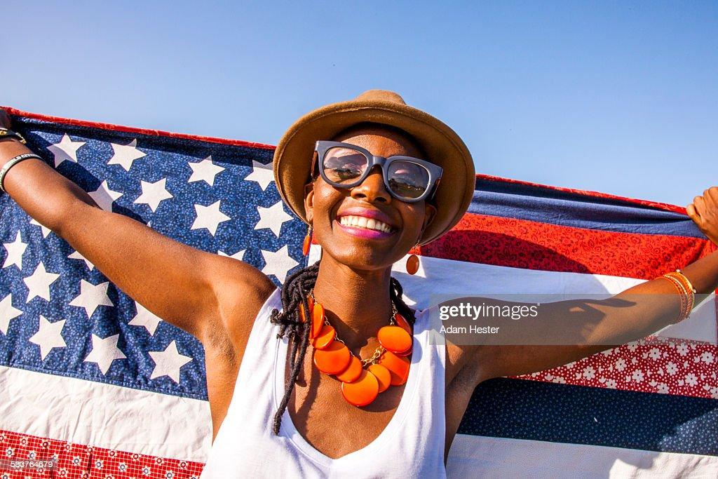 Black woman holding American flag under blue sky : Foto stock