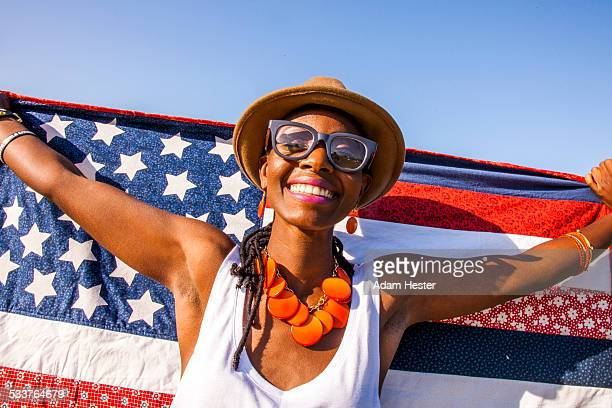 Black woman holding American flag under blue sky
