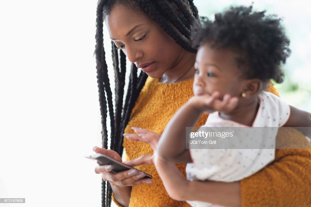 Black woman holding baby daughter using cell phone : Stock Photo