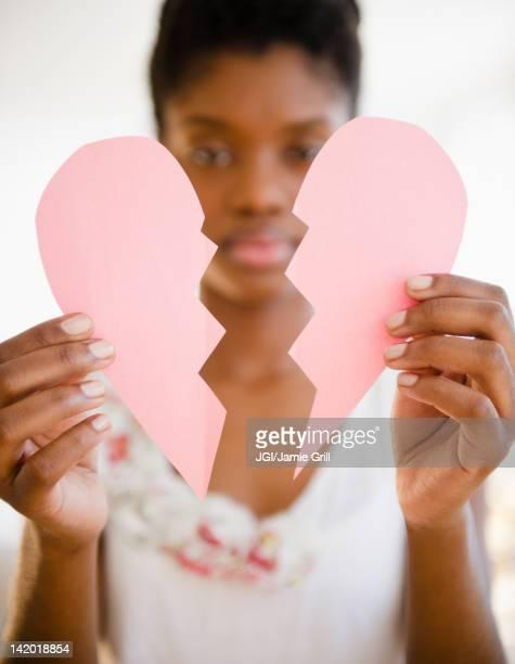 Black woman holding broken paper heart