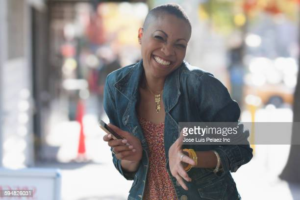 Black woman holding cell phone in city