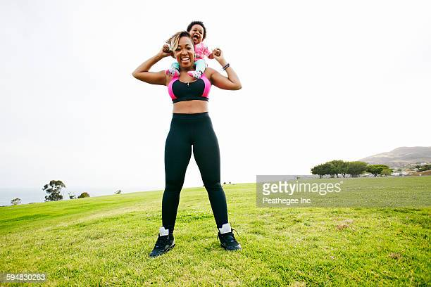 Black woman holding daughter in field