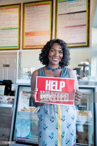 Black woman holding help wanted sign in bakery