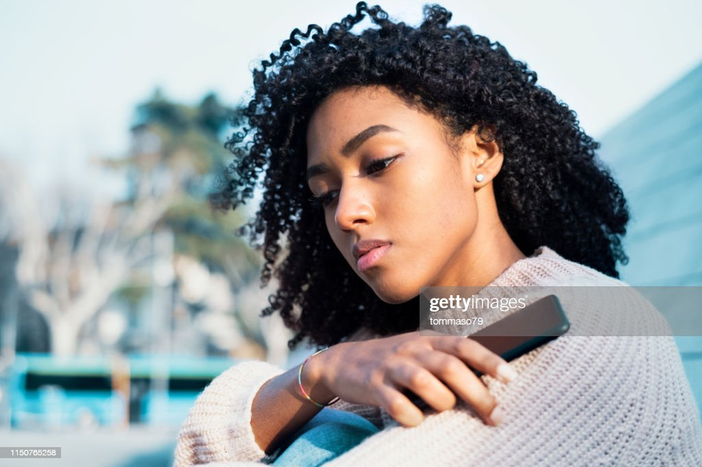 Black woman holding mobile phone outdoor : Stock Photo