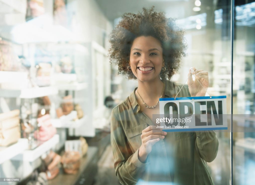 Black woman holding open sign in store window : Stock Photo