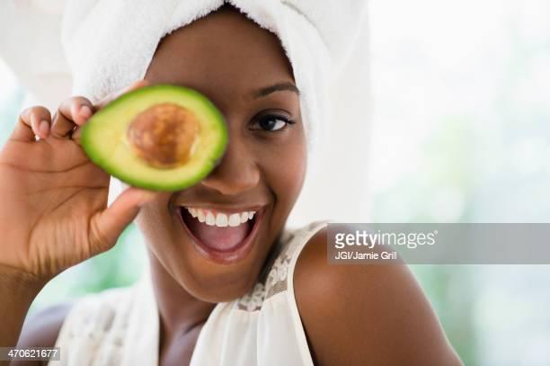 Black woman holding sliced avocado