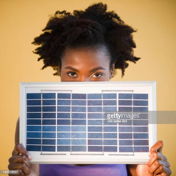 Black woman holding solar panel