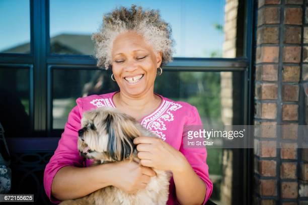 black woman hugging dog near window - personas sin dientes fotografías e imágenes de stock