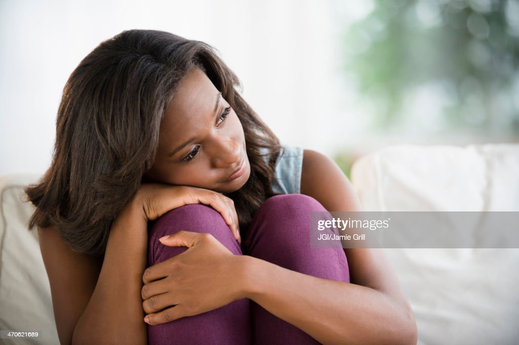 Black woman hugging her knees : Stock Photo