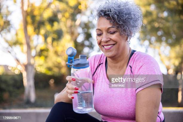 black woman hydrating after workout - drinking water stock pictures, royalty-free photos & images