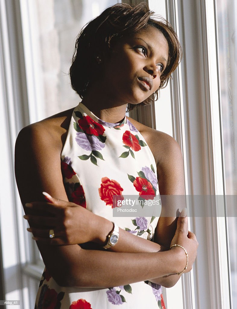 black woman in flower dress looking out window in thought : Stockfoto