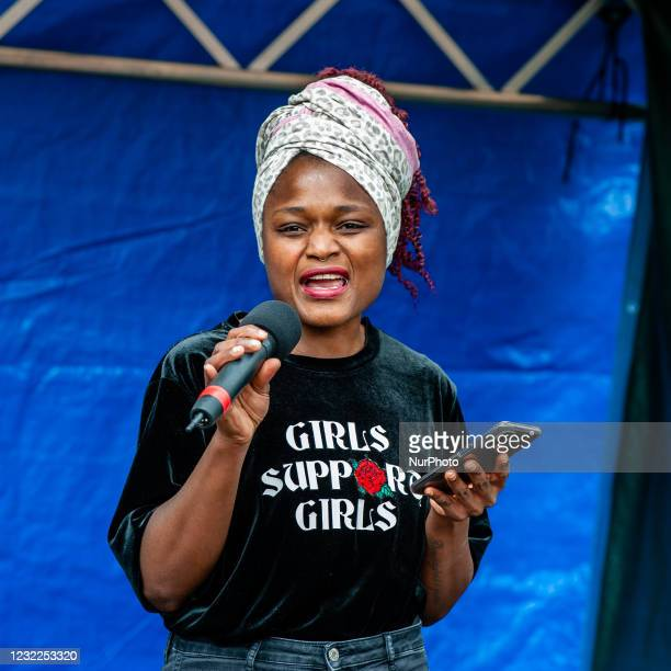Black woman is giving a speech while is wearing a t shirt with the message Girls support girls on it, during the demonstration Reclaim these streets...