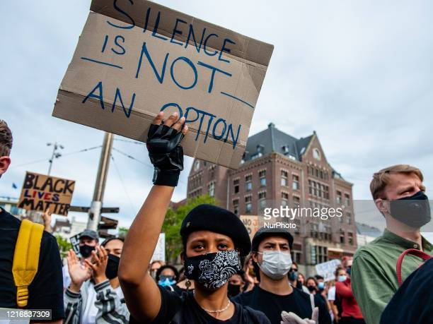 Black woman is holding a placard against racism, during the massive solidarity protest against anti-black violence in the US and EU, that took place...