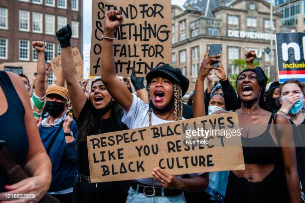 A black woman is screaming while holding a big placard during the massive solidarity protest against antiblack violence in the US and EU that took...