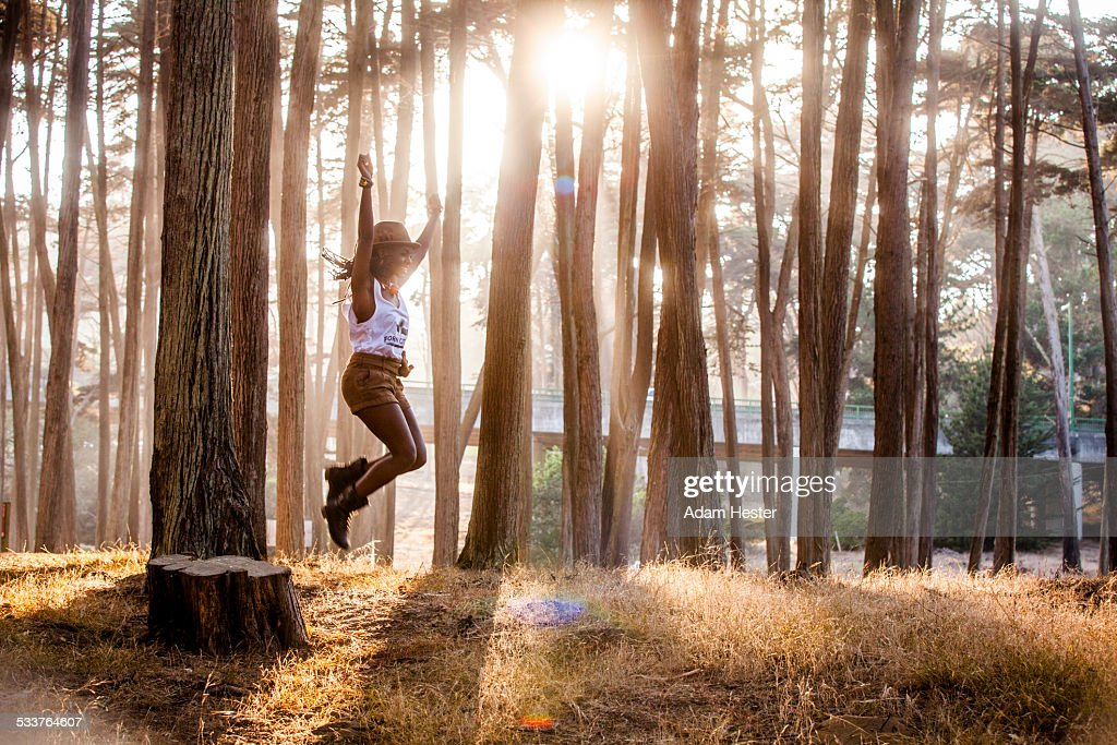 Black woman jumping from stump in sunny forest : Foto stock