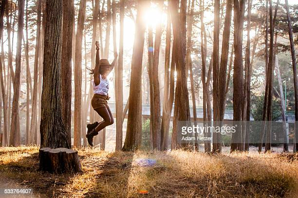 black woman jumping from stump in sunny forest - thick black woman stock photos and pictures