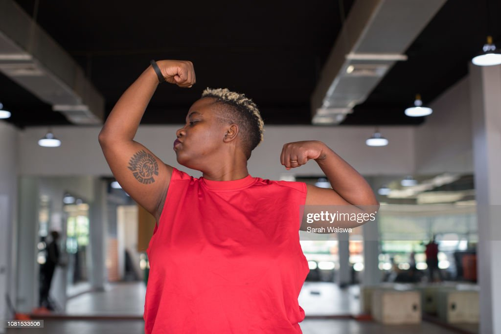 Black woman kissing her muscles at the gym : Stock Photo