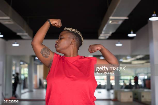Black woman kissing her muscles at the gym