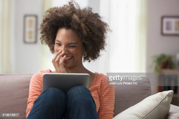 Black woman laughing at digital tablet on sofa
