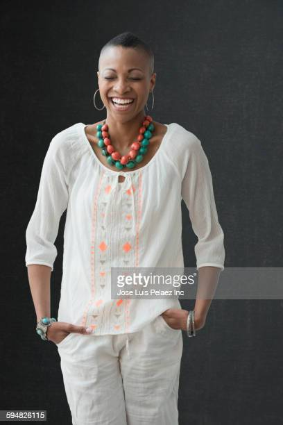 black woman laughing with hands in pockets - hands in pockets stock pictures, royalty-free photos & images